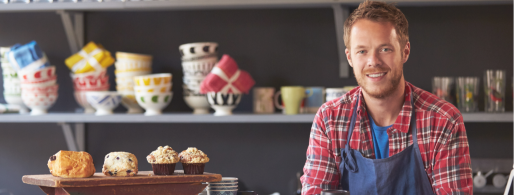 A smiling small business owner sits in his cafe